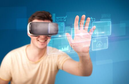containing: Young impressed man wearing virtual reality goggles with blue squares containing data at his fingers Stock Photo
