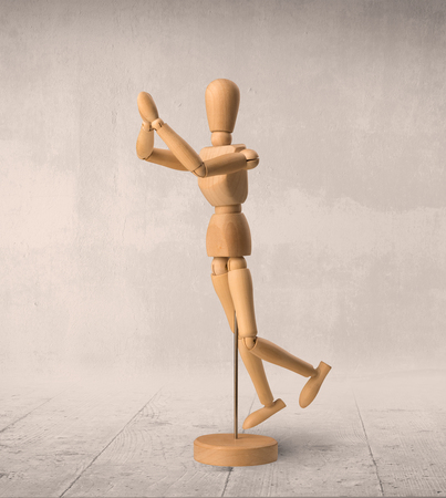 Wooden mannequin posed in front of a greyish background Stock Photo