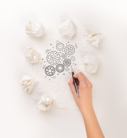 Female hand next to a few crumpled paper balls drawing rotating gears Stock Photo