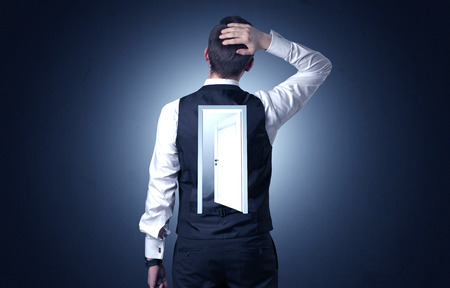 Young businessman standing and thinking with an open door on his back Stock Photo