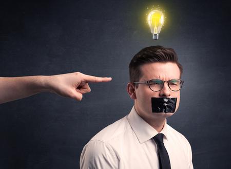 Kaukasische hand die op zakenman met een lightbulb boven zijn hoofd richt