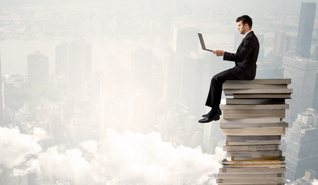 diligent: A serious businessman with laptop tablet in elegant suit sitting on a stack of books in front of cityscape
