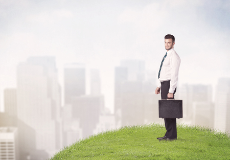 A cheerful caucasian elegant sales manager standing in small green grass in front of faded city landscape, tall buildings concept. Imagens