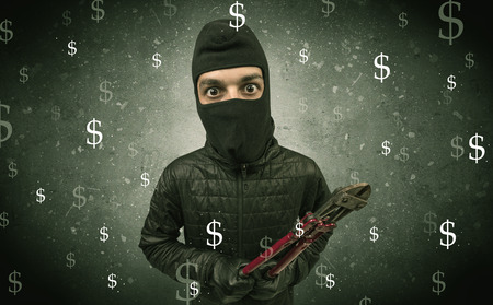 unlawful act: Money hungry thief in black clothes and tolls on his hand. Stock Photo