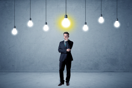Handsome businessman in an empty space with bulbs above and uninspired face Stock Photo