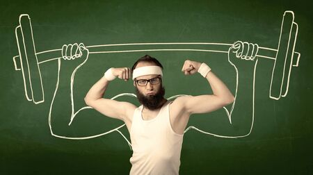 hombre flaco: A young man with beard and glasses posing in front of green background, imagining how he would lift weight with big muscles, illustrated by white drawing concept. Foto de archivo