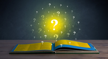 indecisive: Yellow question marks hovering over open book Stock Photo
