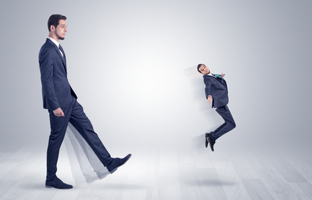 mobbing: Big man in suit kicking out little himself with simple white wallpaper  Stock Photo