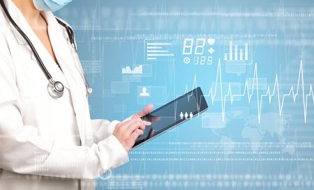 青い背景と心臓関連のチャートでタブレットを保持している女性医師