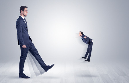 Big man in suit kicking out little himself with simple white wallpaper  Stock Photo