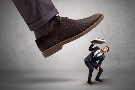 loser: Employee is afraid of the big boss foot, which is stepping down him  Stock Photo