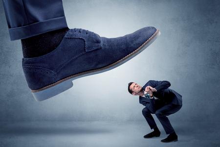 Gran pie intentando aplastar a un hombre pequeño que tiene miedo de eso Foto de archivo