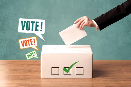 A hand placing a voting slip into a ballot box Standard-Bild
