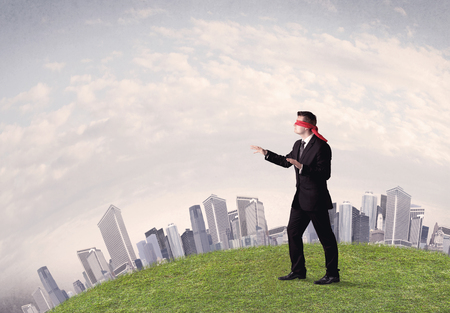 Young blindfolded businessman steps on a a patch of grass with a grey buildings in the background Stock Photo