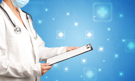 Female doctor holding notepad with blue background and crosses Stock Photo