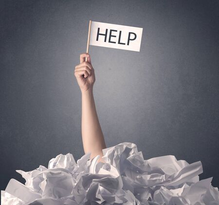 Female hand emerging from crumpled paper pile holding help sign  Stock Photo