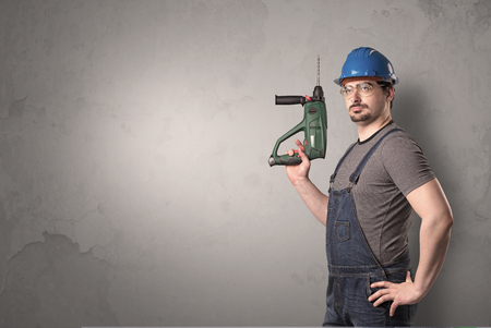 Craftsman standing in front of an empty wall with tool in his hand.