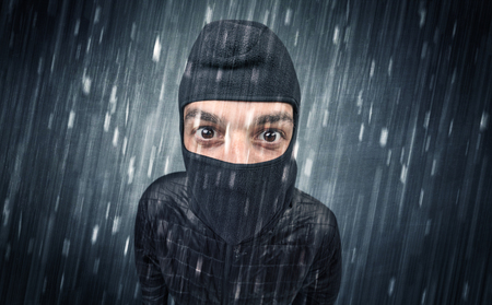 Burglar in action in black clothes with rainy concept.