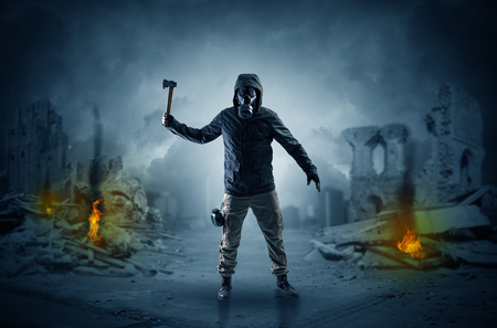 Destroyed place after a catastrophe with man in gas mask and weapon on his hand  Stock Photo