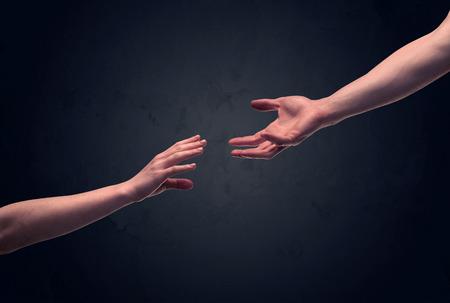 Duas mãos masculinas estendendo a mão para o outro, quase tocando, na frente do conceito de parede de fundo escuro claro vazio Foto de archivo