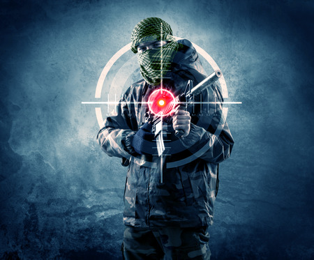 Masked terrorist man with gun and laser target on his body concept  Stock fotó