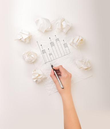 Ženská ruka vedle několika zmačkaných papírových koulí, které kreslily průběžný graf Reklamní fotografie