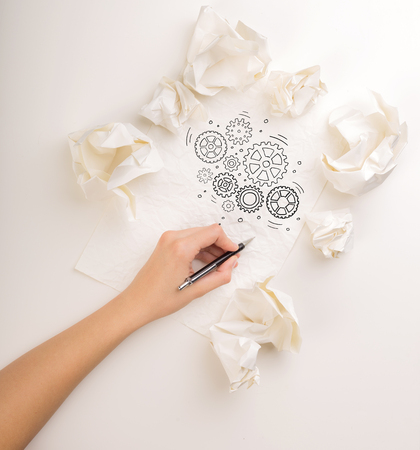 Female hand next to a few crumpled paper balls drawing rotating gears Banque d'images