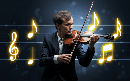 Young handsome fiddler playing with music sheet background Stock Photo