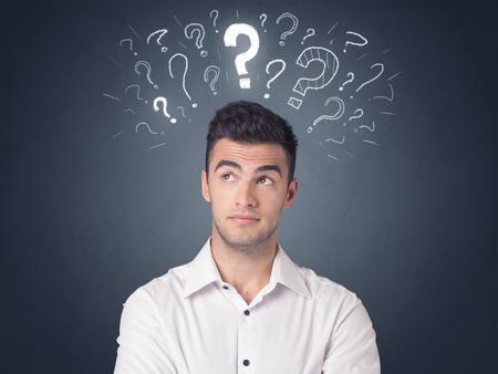 Jeune homme d'affaires décontracté avec des points d'interrogation blancs au-dessus de sa tête Banque d'images