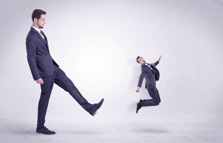 Big man in suit kicking out little himself out with simple white wallpaper