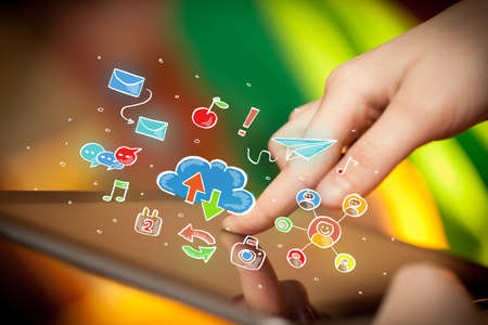 Female hands touching tablet with colorful social media icons Stock Photo