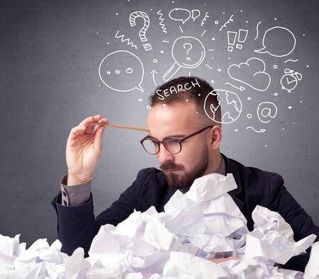Jonge zakenman zitten achter verfrommeld papier met gemengde doodles over zijn hoofd