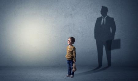 Kleiner Junge stellt sich vor, dass er Geschäftsmann ist und seine Zukunft in einem großen Schatten veranschaulicht