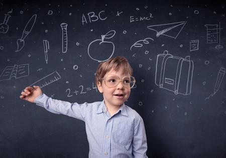Smart little kid in front of a drawn up blackboard ruminate Stock fotó