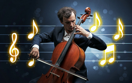 Young handsome cellist playing with music sheet background Stock Photo
