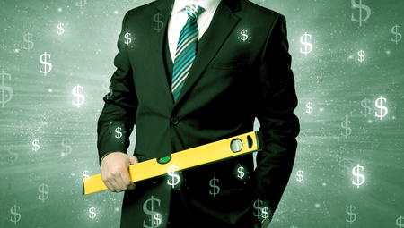 Handsome businessman holding tool with dollar symbols around and with green background Stockfoto