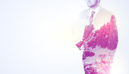 Young businessman in suit standing with sunny snowy mountain and trees graphic. Stock Photo