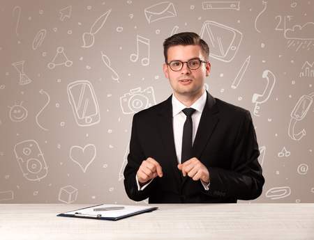 Young handsome businessman sitting at a desk with white mixed media icons behind him