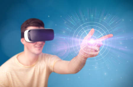 Young impressed man wearing virtual reality goggles with blue circles around his finger  Stock Photo