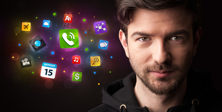 Portrait of a young businessman with colorful applications next to him on a dark background Stock Photo