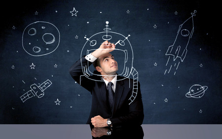 A young happy businessman in elegant suit drawing helmet, satellite and rocket in empty space with a chalk illustration concept Stock Photo