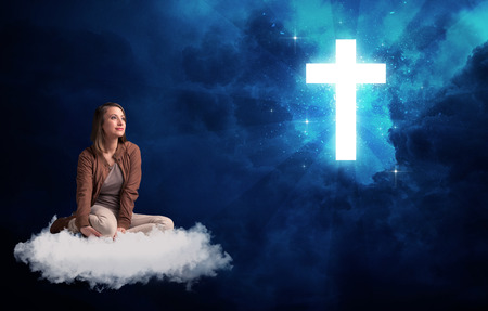 Caucasian woman sitting on a white fluffy cloud looking at a big, bright; blue; glowing cross