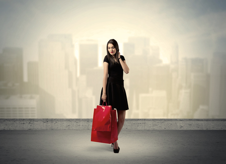Attractive lady in black holding red shopping bags standing in front o urban landscape with tall buildings concept Stock Photo