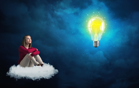Caucasian woman sitting on a white fluffy cloud looking and wondering at a big, bright, shiny, glowing yellow lightbulb