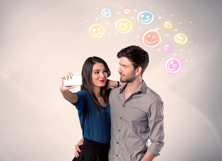 A cheerful young couple taking selfie photo with mobile phone and colorful happy smiley faces illustration above them concept Stock Photo
