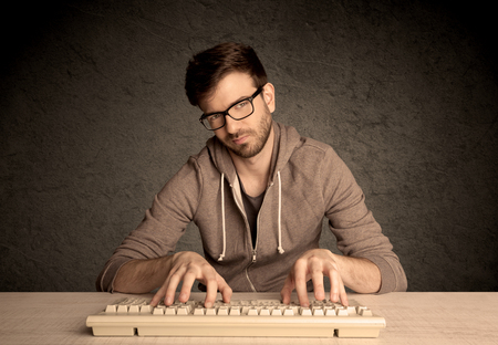 A young hacker with glasses dressed in casual clothes sitting at a desk and working on a computer keyboard in front of black clear concrete wall background concept Stock Photo