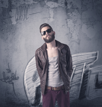 A handsome hipster guy with beard and sunglasses standing in front of an urban wall with graffiti concept Stock Photo