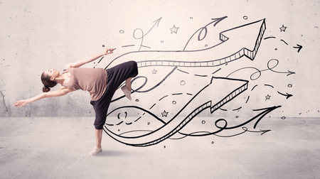 A beautiful young hip hop dancer dancing contemporary street dance in front of urban grey wall background with lines and arrows concept Stock Photo