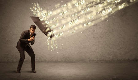 Business man holding umbrella against dollar rain concept on grungy background Stock Photo