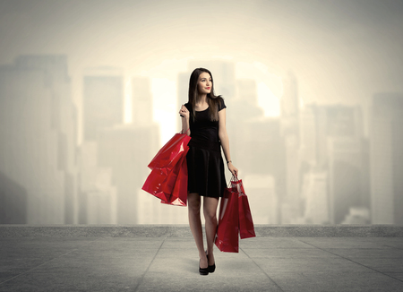 A stylish female standing with red shopping bags on platform and city view landscape backround concept Stock Photo